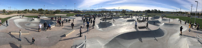 people on bikes and skateboards at skate park